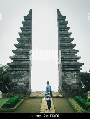 A man stand facing the gate of the Cetho Temple, at Karanganyar, Central Java, Indonesia - Stock Photo