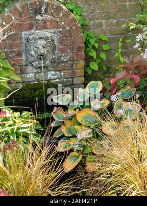 Small water feature with water spouting from stone lion's mouth in brick wall, Barnsdale Gardens, Rutland, England, UK - Stock Photo