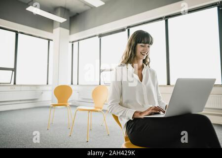 Smiling businesswoman sitting on a chair in an empty office using a laptop