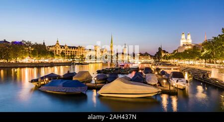 Switzerland, Canton of Zurich, Zurich, Covered boats moored on river Limmat at dusk with old town waterfront in background - Stock Photo