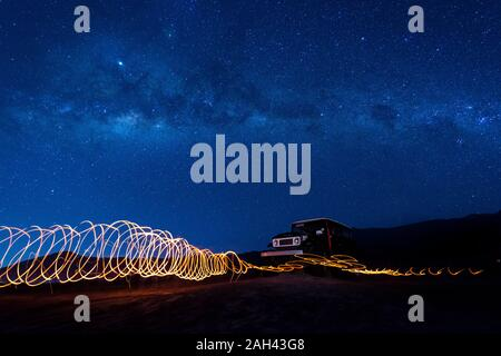 Indonesia, East Java, Spiral light trails in front of car parked in Bromo Tengger Semeru National Park at night - Stock Photo