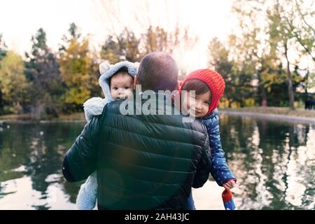 Portrait of two little girls on father's arms in front of a lake at sunset - Stock Photo
