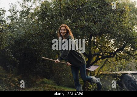 Woman working in her garden, pretending to fly on a shovel
