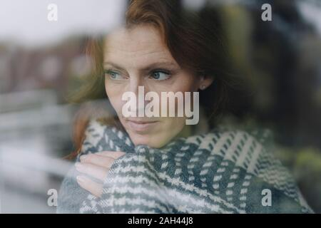 Woman looking out of window, wrapped in blanket - Stock Photo