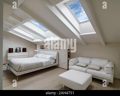 interior shot of a bedroom in the modern attic-room in the foreground the leather sofas with footrest in the background there is the bed illuminated b