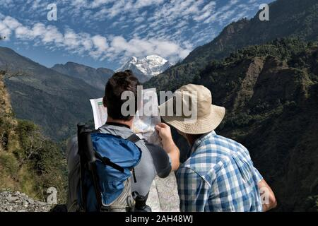 Two hikers reading map at Muri, Dhaulagiri Circuit Trek, Himalaya, Nepal - Stock Photo