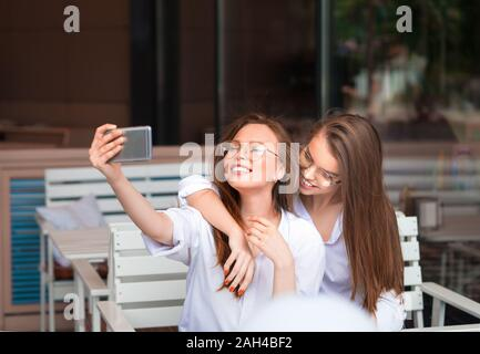 Cheerful female friends taking selfie picture in cafe. Two beautiful young women smiling and looking to the camera of smartphone. Friendship concept