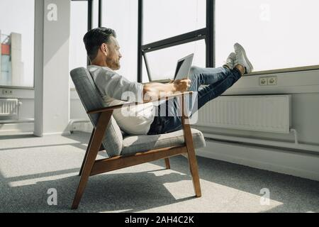 Mature businessman using laptop in empty office