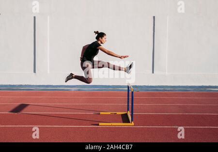 Female hurdler during training on tartan track - Stock Photo