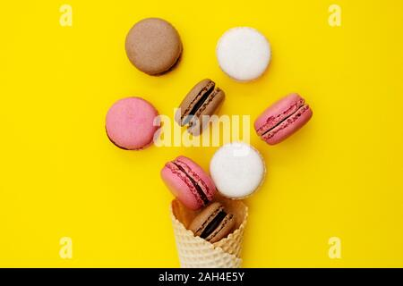 Macarons cakes. Stil life photo of waffle cone with macaroons on yellow background. Flat lay, dessert. - Stock Photo