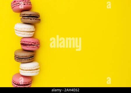 Macarons cakes. Fashion or feminine background delicious macaroons in row on yellow background. Flat lay social media walpaper. Copy space. - Stock Photo
