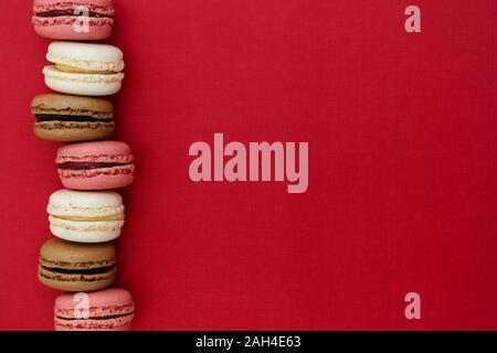 Macarons cakes. Abstract food photo background with delicious macaroons over red background. Flat lay social media walpaper. Copy space. - Stock Photo