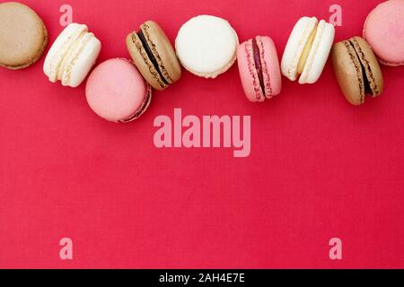 Macarons cakes. Abstract Christmas food photo background with delicious macaroons over red background. Flat lay social media walpaper. Copy space. - Stock Photo