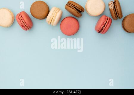 Macarons cakes. Abstract food photo background with delicious macaroons over blue background. Flat lay social media walpaper. Copy space. - Stock Photo