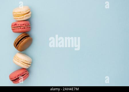 Macarons cakes. Fashion or feminine background delicious macaroons in row on blue background. Flat lay social media walpaper. Copy space. - Stock Photo