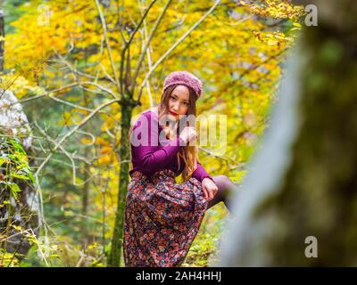 Country-girl countrygirl in countryside isolated serious looking at camera eyeshot eyes-contact put one leg up on tree posture pose posing - Stock Photo