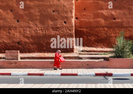 A woman in red walks along a pavement