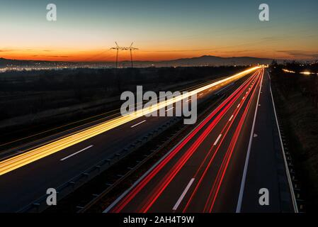 Cars light trails on a straight highway at sunset. Night traffic trails, Motion blur, Night city road with traffic headlight motion. - Stock Photo