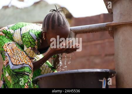 Nicely Braided African Girl Washing Her Face With Fresh Water At the Borehole - Stock Photo