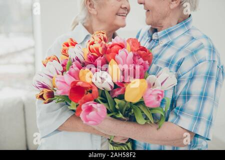 Cropped portrait of her she his he two nice cheerful cheery sweet, tender people granny receiving big fresh tulips congratulations greetings spring in - Stock Photo