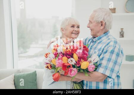 Portrait of her she his he two nice attractive cheerful cheery sweet, tender people granny receiving fresh floral tulips congratulations greetings spr - Stock Photo