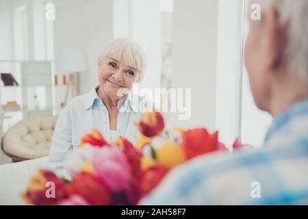 Two nice attractive beautiful kind cheerful cheery sweet people granny, receiving fresh natural floral tulips congratulations spring in light white in - Stock Photo