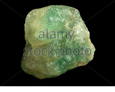Raw fluorite or fluorspar mineral stone in front of black background, mineralogy and esotericism - Stock Photo