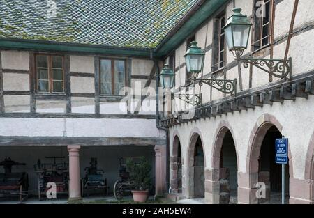 Ungersheim, Haut-Rhin / France - 13. December, 2019: view of a historic half-timbered Alsation country house and courtyard with old horse-drawn carria - Stock Photo