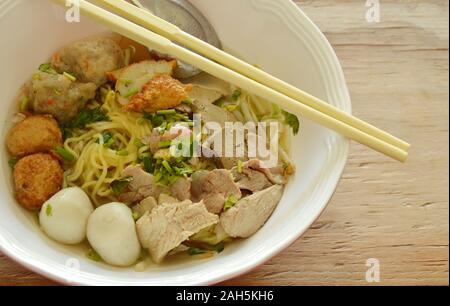 yellow noodles topping fish ball and slice boiled pork in soup - Stock Photo