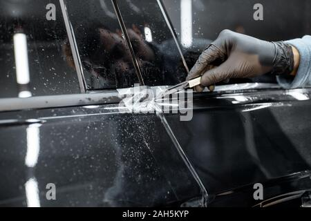 Worker trimming with cutter remains of a protective film, sticking it on a car body at the vehicle service - Stock Photo