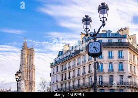 Paris, the Saint-Jacques tower, with typical buildings in the center, and a clock in the street - Stock Photo
