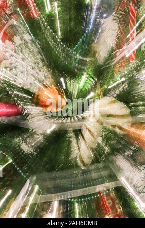 Abstract blurry photo of christmas tree with motion zoom effect, defocused colorful xmas ornaments.