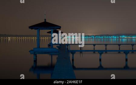WUHAN, HUBEI / CHINA - NOV 20 2019: Night view of  Chinese Pavillion and Chinese bridge with light decoration at East Lake and city skyline on backgro - Stock Photo