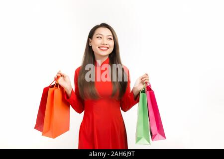 Vietnamese woman wearing traditional ao dai clothes and holding shopping bags in lunar New Year festival - Stock Photo