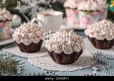 Homemade chocolate cupcakes with cream and a cup of coffee arranged on a light blue background, horizontal orientation
