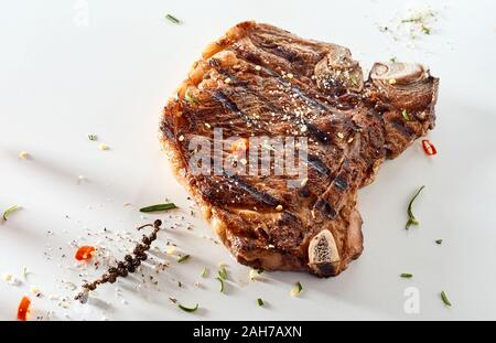 Grilled cowboy steak or bone-in ribeye seasoned with chilli, herbs and spices on a white background with copy space - Stock Photo