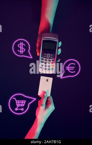 Concept of online or wireless payments. Hands with pinpad and credit card with payment icons. Modern neon color. - Stock Photo