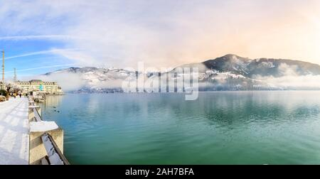 Zell am See, Austria - Dec 2019: Lake Zell in the Austrian Alps in winter. Panoramic view of lake, foggy mountains and Esplanade leading to Grand Hote - Stock Photo