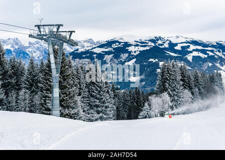 Mountains ski resort Zell am See Kaprun, Austria. Beautiful white winter landscape with snow, cable car over fir tree forest and snow cannon in snow-c - Stock Photo