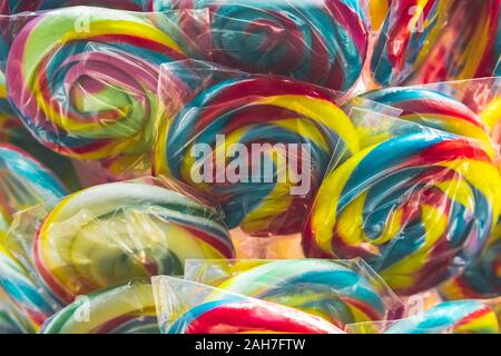 Group of vivid colored lollipops in the display for sale at a candy store in individual plastic packaging, selective focus. - Stock Photo