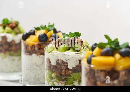 selective focus of fresh granola with kiwi and canned peach with blueberries isolated on white - Stock Photo