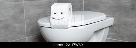 Panoramic shot of toilet paper with smile sign on white toilet bowl in bathroom - Stock Photo