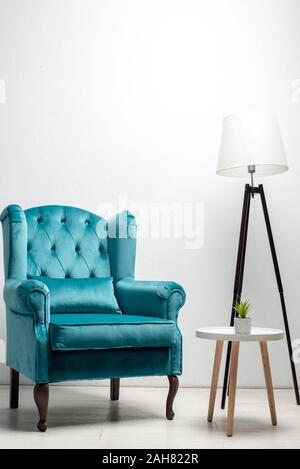 elegant velour blue armchair with pillow near coffee table and floor lamp - Stock Photo