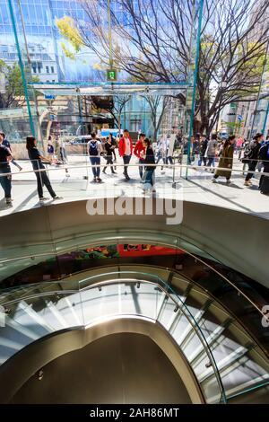 Interior of the Apple store in Omotesando, Tokyo. Spiral staircase to basement level, with the entrance top the shop in the background. Glass building - Stock Photo