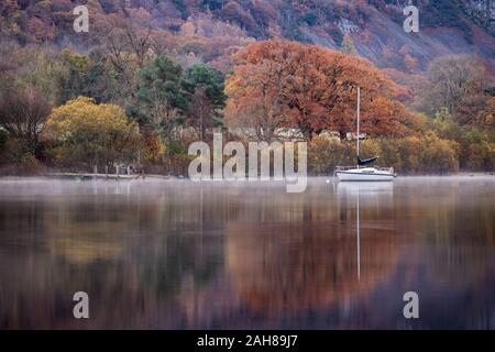 Moored yacht and reflections with mist rising on Derwent Water at Autumn time in the English Lake District, Cumbria. - Stock Photo