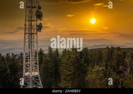 Telecommunications tower, antenna and satellite dish over Sumava forest. - Stock Photo