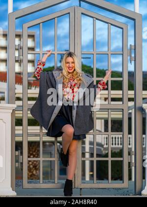 Fanciful blonde young lady spreading on metal fence door entrance looking at camera eyeshot eyes eye-contact forsed chuckle smile - Stock Photo