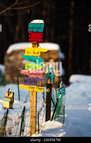 Colorful bird houses and signs with snow on the ground in winter - Stock Photo