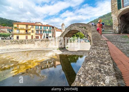 Tourists, including an attractive younger couple, sightsee near the Monet arched bridge in the medieval village of Dolceacqua, Italy. - Stock Photo