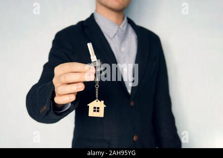 Holding house keys on house shaped keychain concept for buying a new home. guy in the suit shows me the keys. Key chain in the form of a house in a ma - Stock Photo